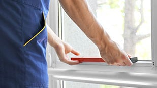 Man using level to check replacement window