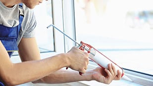 Man uses caulking to install replacement window